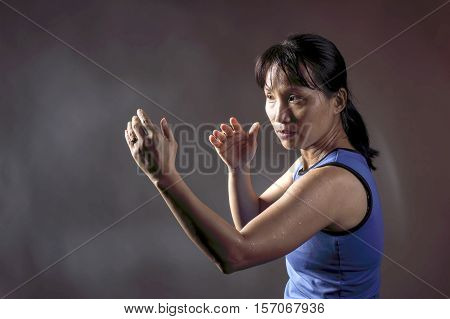 Woman in fight position. An asian woman poses in a fighters position.