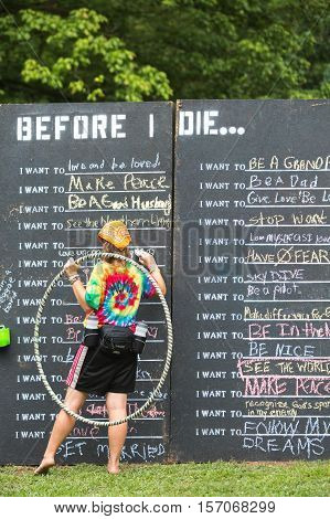 Woman Writing On Wish List Chalkboard