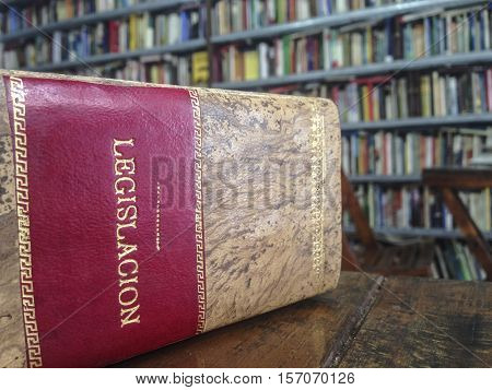 Law book in spanish over table. Library shelves background