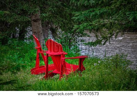 Two red Adirondack chairs sitting by a river.