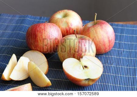Whole and sliced striped red apples on a blue place mat
