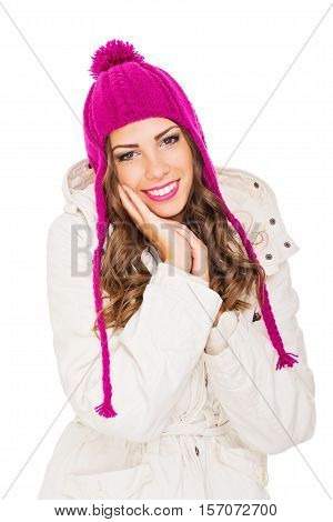 Beautiful young woman in pink knitted beanie hat and winter jacket. Modern cute teenage girl in beige and pink outerwear, studio lighting, medium retouch.