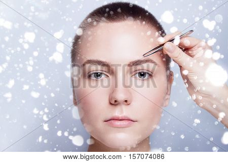 Young woman with short hair plucking eyebrows with tweezers close up woman plucking eyebrows depilating with tweezers. beauty people winter and health concept . over snow on gray background