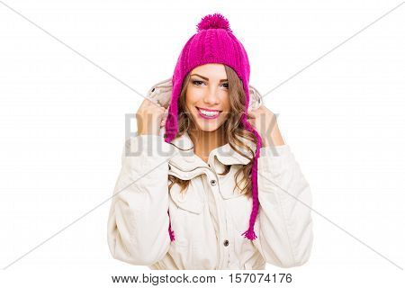 Gorgeous young woman in pink knitted beanie hat smiling. Closeup studio portrait of beautiful blonde teenage girl in modern winter outerwear. Isolated on white, medium retouch, studio lighting.