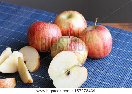 Striped Gala apples whole and sliced on a blue place mat