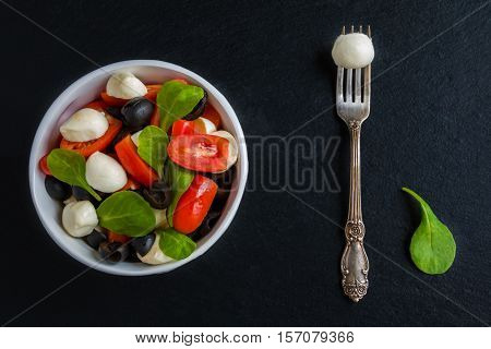 Caprese Salad, Small Mozzarella Cheese, Fresh Green Leaves, Black Olives And Cherry Tomatoes In Whit