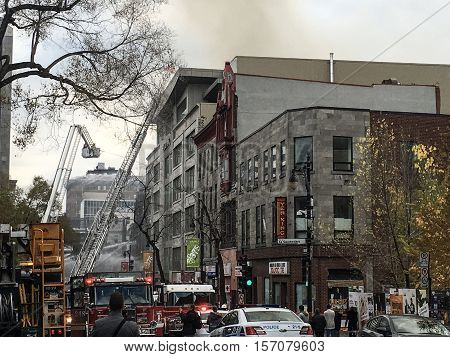 Montreal,Canada, Nov 17, 2016 : Scene on the street in Montreal where Canada's first movie theatre, a Heritage Historic building built in 1879 burns down with fire trucks, police and firemen working to put out the fire.