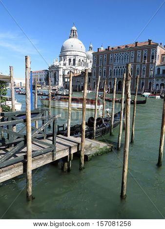 Boats and gondolas along a canal in Venice Italy with Basilica di Santa Maria della Salute