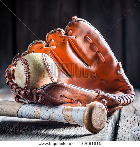 Golden Glove And Old Baseball Ball On Old Wooden Table