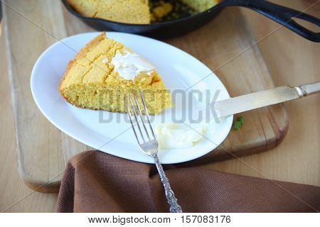 Cornbread wedge with butter with cast iron skillet in background