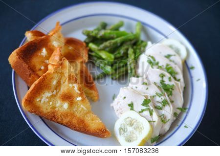 Poached chicken slices with garlic bread and asparagus