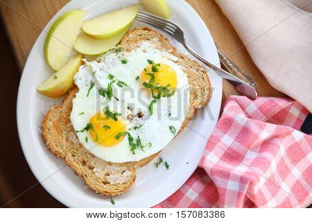 Overhead view of fried eggs on toast with coarse salt and apple slices