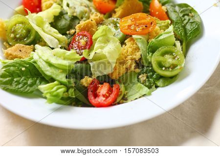 Closeup of butter lettuce and spinach salad with crumbled cornbread
