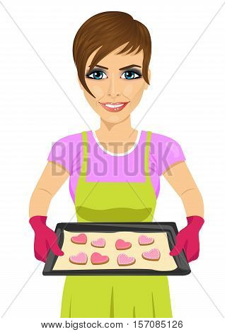 young woman holding baking tray with heart shape cookies over white background