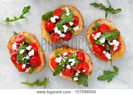 Crostini Appetizers With Cherry Tomatoes, Arugula, And Cheese, Above View On White Marble