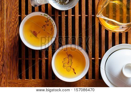 Chinese tea ceremony, shen puer tea, transparent glass, Pialats, tea set on a wooden table. Close up, top view concept.