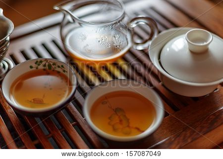 Chinese tea ceremony, shen puer tea, transparent glass, Pialats, cup, tea set on a wooden table. Close up concept.