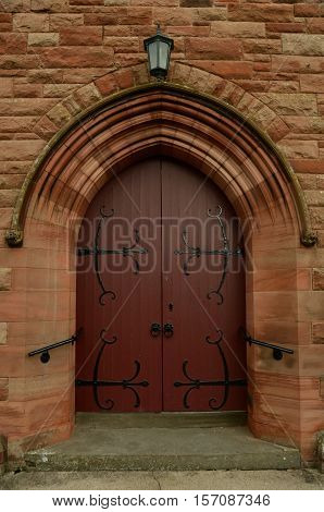 A view of a wooden church door with ornate hinges in Scone