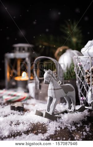 Christmas composition with rocking horse, candle, christmas ball and decoration on black background with snow. Christmas greeting card. Copy space.