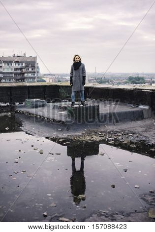 Young Girl On Roof Skyscaper Reflected In A Puddle