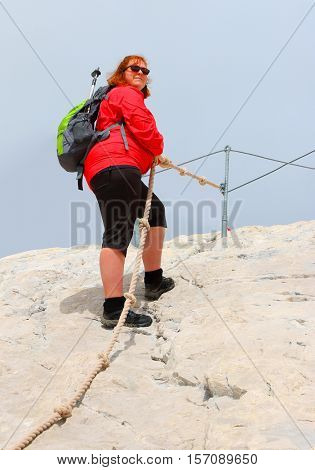 Overweight hiker woman on the top of peak. Zugspitze summit, Germany.  Active people enjoying outdoor sports in mountain landscape. Healthy lifestyle and slimming concept.