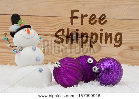 Free Shipping message Some snow Christmas ornaments and a snowman on weathered wood with text Free Shipping