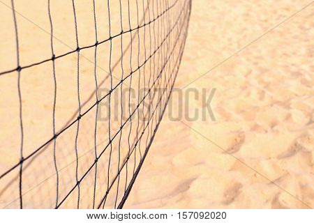 indistinct black grid for playing beach volleyball closeup against the background of the sand