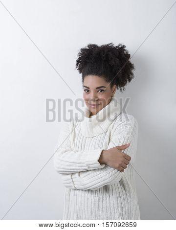 Woman in turtleneck, studio portrait at white wall