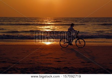 GOA INDIA - NOVEMBER 21 2007: An unidentified young girl cycles on the beach at sunset