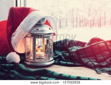 Christmas winter background-lantern with candle and Santa hat on the windowsill with winter nature outside. Christmas festive winter still life. Concept of Christmas at home cosy Christmas still life