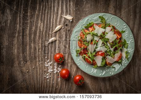 Rocket Salad With Cherry Tomato And Pecorino In Plate On Wooden Tacbe, Top View