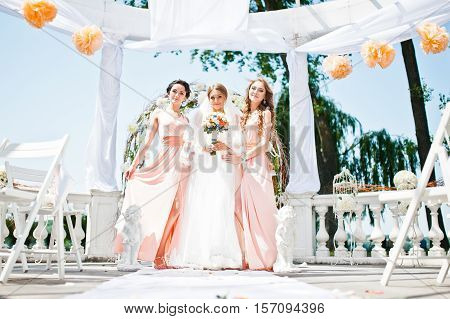 bride with bridesmaids at wedding ceremony at sunny day