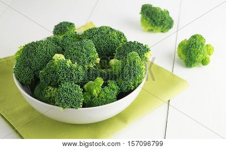 Raw broccoli in bowl on white table. Green vegetable horizontal selective focus