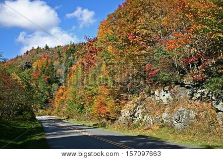 the Blue Ridge Parkway in North Carolina winds beneath hillsides covered with colorful autumn foliage