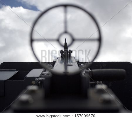 Sighting a vintage WWII gun pointed towards the sky, war concept point of view