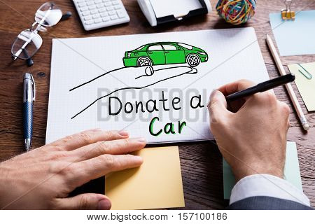 Businessperson Drawing Concept Of Car Donation On Notebook
