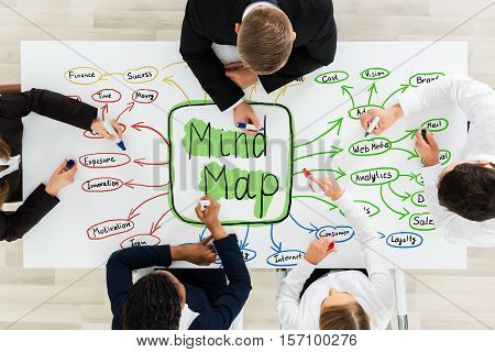Businesspeople Drawing The Concept Of Mind Map On Desk