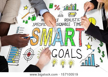 Businesspeople Discussing Smart Goal Concept On Desk