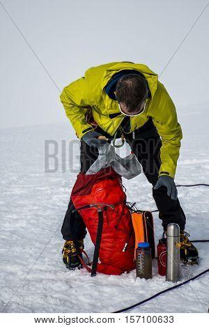 Men Hiking the glacier Hvannadalshnukur highest summit in Iceland mountain landscape Vatnajokull park packing backpack