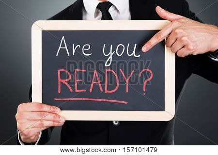 Close-up Of Businessman Showing Are You Ready Text Written On Slate At Grey Background