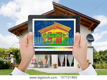 Close-up Of The Person Detecting Heat Loss Outside The House Using Digital Tablet