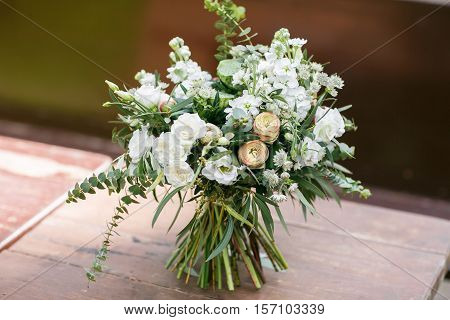 Bridal bouquet. The bride's bouquet. Beautiful bouquet of white flowers and greenery, decorated with silk ribbon, lies on vintage wooden chair