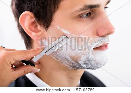 Close-up Of A Hairdresser Shaving Man's Beard By Applying Shaving Cream