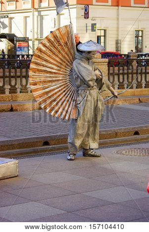 ST PETERSBURG RUSSIA - JANUARY 01 2016: a performer - Silver painted artists on a city street living statues