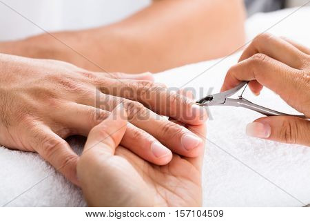 Close-up Of A Manicurist Cutting Off The Cuticle From The Person's Fingers