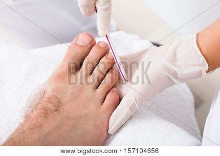 Close-up Of A Beautician Hand Filling Person's Nail In Salon