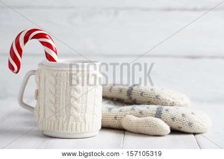 Knitted winter cup of hot drink with a candy cane and mittens on white wooden background