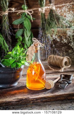 Aromatic Tincture With Alcohol And Herbs On Old Wooden Table
