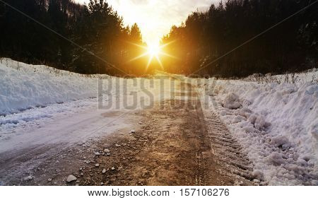 Snow covered winter road with shining streetlights  in rural areas