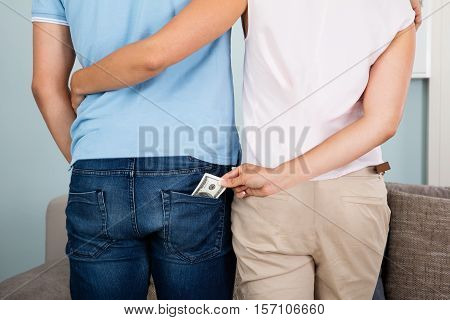Rear View Of Woman Stealing Money From Husband's Pocket Without Acknowledging Him